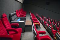VIP chair in an empty cinema among red chairs.