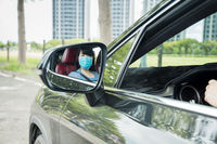 Woman in protective mask driving  car on the  road