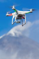 Flying UAV drone quadcopter aerial videography in sky on background volcano eruption. Focus foreground