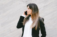 Close up, businesswoman in suit. Businesswoman with serious expression talking phone outdoors.
