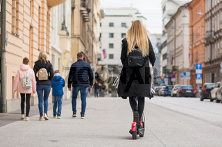 Rear view of girl riding public rental electric scooter in urban city environment. New eco-friendly modern public city transport in Ljubljana