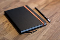 Black business notebook and regular pencil on a vintage wooden desk