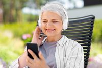 old woman with headphones and smartphone at garden