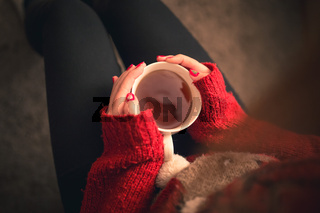 Top down shot of a Girl with a warming tea drink in hands sitting on the sofa with christmas colored fingernails and reindeer sweater.