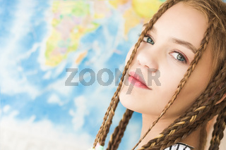 Portrait of a beautiful girl face close-up on a world map background. Soft natural light
