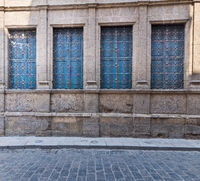 Windows with ferforge wrought iron grill and blue shutters on old stone bricks wall, and basalt road