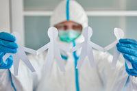 Mitarbeiterin hält Scherenschnitt von Team als Dekoration in Kinderklinik