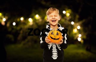 happy boy in halloween costume with jack-o-lantern