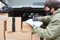 Paketbote mit vielen Paketen im Kofferraum vom Lieferwagen
