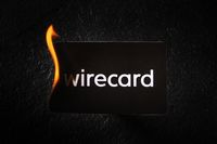 Madrid, Spain - June 27, 2020: Wirecard prepaid card burning on fire following the company bankruptcy and the freezing of cardholders' money