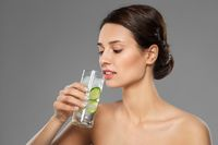 woman drinking water with cucumber and ice