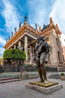 Guanajuato, Mexico - February 26, 2020: La Giganta bronze sculpture by Jose Luis Cuevas with Juarez Theater in the background.