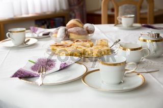 Table with coffe or tea cups, cake, plates