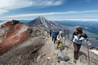 Group of hikers climbing to crater of active volcano