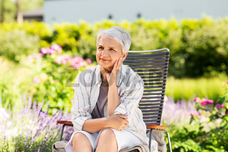 happy senior woman resting at summer garden