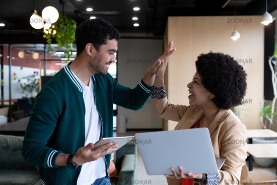 Diverse businessman and businesswoman using laptop and tablet high fiving in office