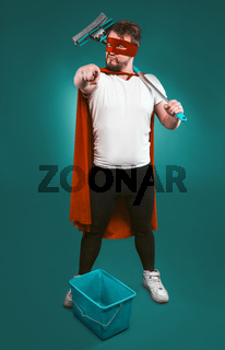 Superhero is ready to fight for cleanliness, Brave man in a red superhero uniform with a bucket and a mop points the camera with his index finger. Cleaning concept. Isolated on green