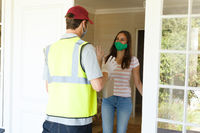 Caucasian woman wearing face mask taking package from delivery man at front door