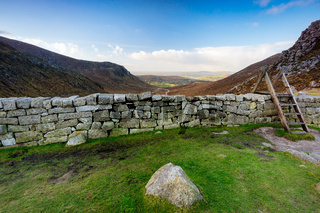 Mourn Wall with ladder on the Hares Gap overseeing beautiful valley with blue sky and white clouds