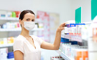 female customer in mask choosing drugs at pharmacy