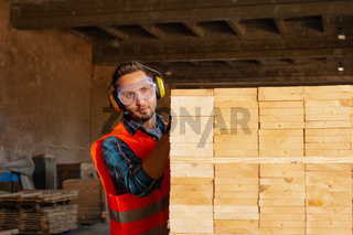 Busy young professional woodworker using equipment wooden plank
