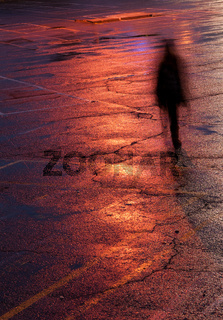 Person walking alone in the dark under bright orange light after rain.