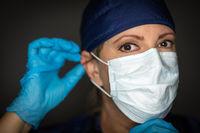 Female Doctor or Nurse Wearing Surgical Gloves Putting On Medical Face Mask