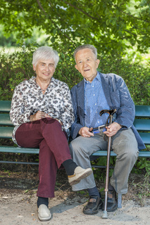 Happy retired couple on the park bench