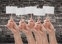 Five Female Hands Holding Blank Signs Against Aged Brick Wall