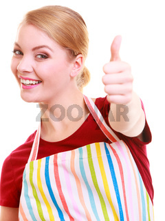 Happy housewife in kitchen apron showing thump up hand sign