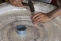 Silberschmied graviert eine Silberplatte mit Hammer und Meissel, Ban Phanom, Laos