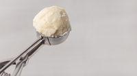 Kugel Vanilleeis im Eisportionierer einer Eisdiele