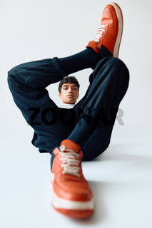 Young trendy mixed race man posing in studio lying on floor on white background