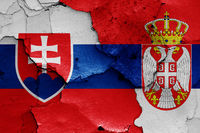 flags of Slovakia and Serbia painted on cracked wall