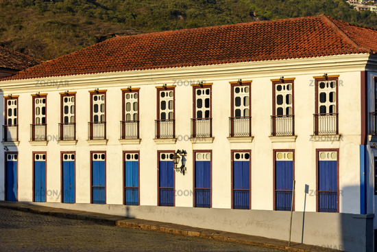Facade of old house in colonial architecture with blue, brow and yellow windows and doors