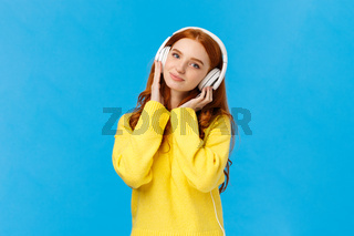Waist-up shot tender and cute, lovely redhread woman in yellow sweater, tilt head, wear headphones, touching earphones as press to ears, listen music, smiling camera delighted, blue background
