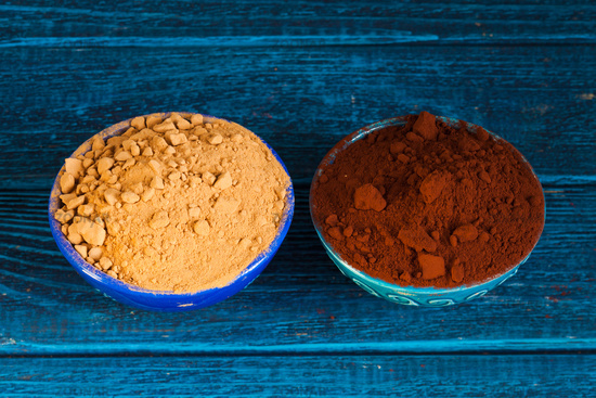 Organic carob and cacao powder in bowls. Natural cocoa substitute.