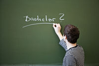 Young man writing Bachelor on a chalkboard