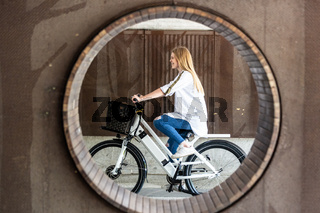Casual caucasian teenager riding urban electric bicycle in urban environment. Urban mobility concept