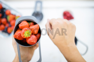 Female hands holding measuring cup full of fresh strawberries