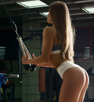 Sexy blonde trainer exercising shot in sports gym