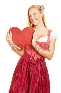 Frau im Dirndl hält rotes Herz