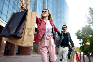 Front view of a casual couple of shoppers running in the street towards camera holding colorful shopping bags.