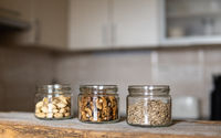 Sunflower seeds, walnut and almond in a jars which standing on a white vintage table with a kitchen on background. Nuts is a healthy vegetarian protein and nutritious food. Nuts on rustic old wood.