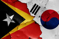 flags of East Timor and South Korea painted on cracked wall