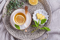 Healthy detox ginger and sage tea with lemon on tray