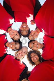 Female soccer team forming huddle against sky