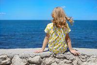 Little girl sitting on seashore in summer day