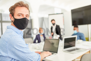 Business Mann mit Mundschutz am Laptop