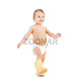 cute little boy walking in big rubber boots